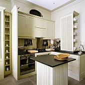 Light gray built in kitchen in elegant country house style and square island with a black work surface