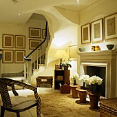 Atmospheric lighting in a living room of a villa with a flight of stairs and white flowers in pots standing in front of the fireplace