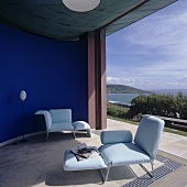 A living room with upholstered loungers in front of a curved, blue-painted wall and a view of the sea