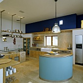 The charm of various materials - a blue-painted, round island counter with concrete kitchen furniture with wooden door in the background