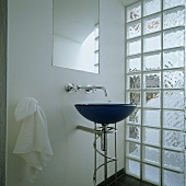 A blue, free-standing wash basin in front of a glass brick wall and a wall tap under a mirror