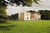 Ballinlough Castle Gardens - Wiesenfläche vor irischer historischer Schlossanlage teilrenoviert mit Ecktürmen und Zinnen