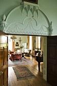 Stuckverzierung an der Wand über geöffneten Flügeltüren mit Blick auf eleganten Wohnraum eines Schlosses