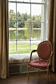 A pink padded chair with a gilded frame in front of a window with a view