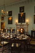 A Baroque room in a castle with a fireplace and a festively laid, candlelit dining table