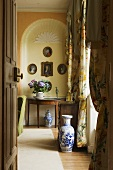 Blick durch offene Tür auf eine blau weisse Bodenvase und Beistelltisch vor gelbgetönter Wandnische