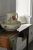 A washing bowl with a jug on a wall table with drawers