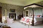 Elegantes Schlafzimmer eines Schlosses mit antiker Sitzbank am Himmelbett mit Baldachin vor Wand mit floralem Tapetenmuster