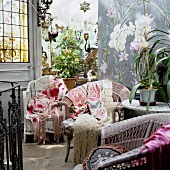 Wicker chairs with colourful throws and potted plants in a side room looking into a conservatory