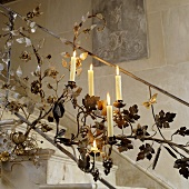 Burning candles in a metal banister featuring a floral design and candle holders
