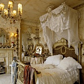 A Rococo-style bedroom - a four poster bed with white bedclothes and a lace canopy
