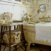 Bathing utensils on a wicker side table next to an antique bathtub with feet and brass taps