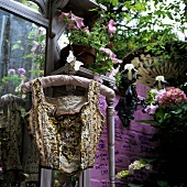 Paillette vest on a coat hanger in front of a pink wall with plant pots