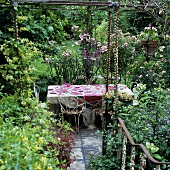 Rusty garden furniture, a floral tablecloth and a candle stick