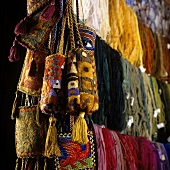Coloured strands of wool and oriental shoulder bags hanging up