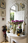 A bunch of flowers on a white wall table in front of a mirror with a carved wooden frame