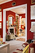 A living room with red walls and a white framed doorway with a view onto an illuminated mirror and a fireplace