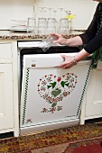 A dishwasher with a heart and animal motif being filled up