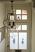 A chandelier with beads and glass droplets in the hallway of an old residential house