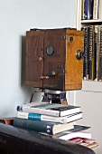 Antique film camera in a wooden case in front of a book shelf