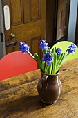 Blue hyacinths in a brown earthenware jug on an old wooden table