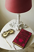 An arrangement on a white occasional table - a table lamp with a red shade, a Venetian mask and a red-bound book