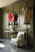 A white armchair, an occasional table, a wall table and a floor lamp in front of a dark wood-panelled wall with red decorations