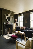 A dark painted fireplace room with green wooden panelling and a pink upholstered stool with an occasional table on the floor boards in front of the fireplace