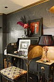 A home office set up on an antique davenport against a black wall with a stool in front of it