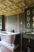 A vintage bathtub on a pedestal with wall taps in a painted room