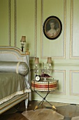 A bedroom with green wood panelling and gilded borders and an old drum being used as a bedside table