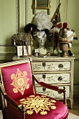 A baroque wooden chair upholstered in shiny red with a gold pattern in front of a painted chest of drawers