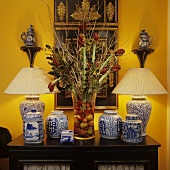 Chinese vases with plissé shades and porcelain on a chest of drawers with a bunch of amaryllis against a bight yellow wall