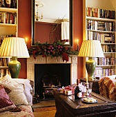 Atmospheric lighting in a room with a fireplace and a built-in bookshelf in front of a red wall