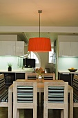 A redish orange lampshade hanging over a light wooden dining table and chairs in front of an open-plan, fitted kitchen