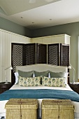Baskets at the foot of a double bed with a headrest and a dark wooden lattice paravent