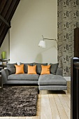 A grey sofa with orange cushions and a grey flokati rug under the slopping ceiling