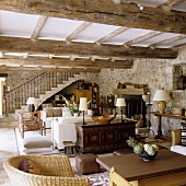 An open living room with a natural stone wall and a dining area under a rustic wooden beamed ceiling and view of a flight of stairs