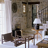 Leather chairs and an occasional table in front of a natural stone wall and a flight of stairs with black metal banisters