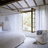 A white bedroom in a country house - a four poster bed covered with light fabric in front of an open window