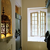 A hallway in a rustic country house - oriental lanterns in a wall niche and an open transom window