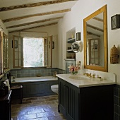 A bathroom in a country house with a terracotta floor - dark wood panelling on a wash basin and a bathtub in front of an open window