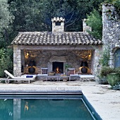 A pool and an open-fronted Mediterranean-style building with atmospheric lighting in front of a natural stone wall and a fireplace
