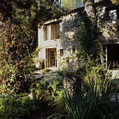 A Mediterranean country house with a natural stone facade, wooden transom windows and an overgrown garden