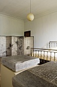 Art in a bedroom - engraved stones on pedestals at the foot of a stainless steel bed