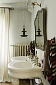 An antique, free-standing wash basin with two sinks and a mirror