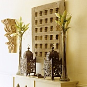 Oriental metal lanterns and lilies in glass vases in front of a rustic wooden latice