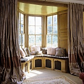 Open curtains in front of a bay window with a view and a built-in window seat with pink cushions