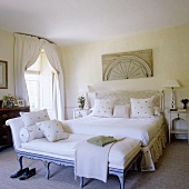 A light coloured bedroom in a country house with a chaise lounge in front of a double bed with white bedclothes