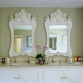 A marble table top with two wash basins and white-framed mirrors on a grey-painted wall